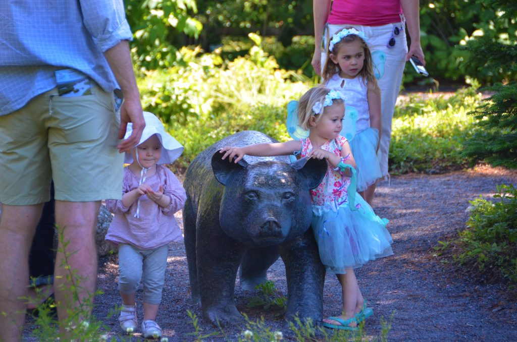 Children dressed up as fairies enjoying the bronze statue of Sal's Bear, inspired by Blueberries for Sal.