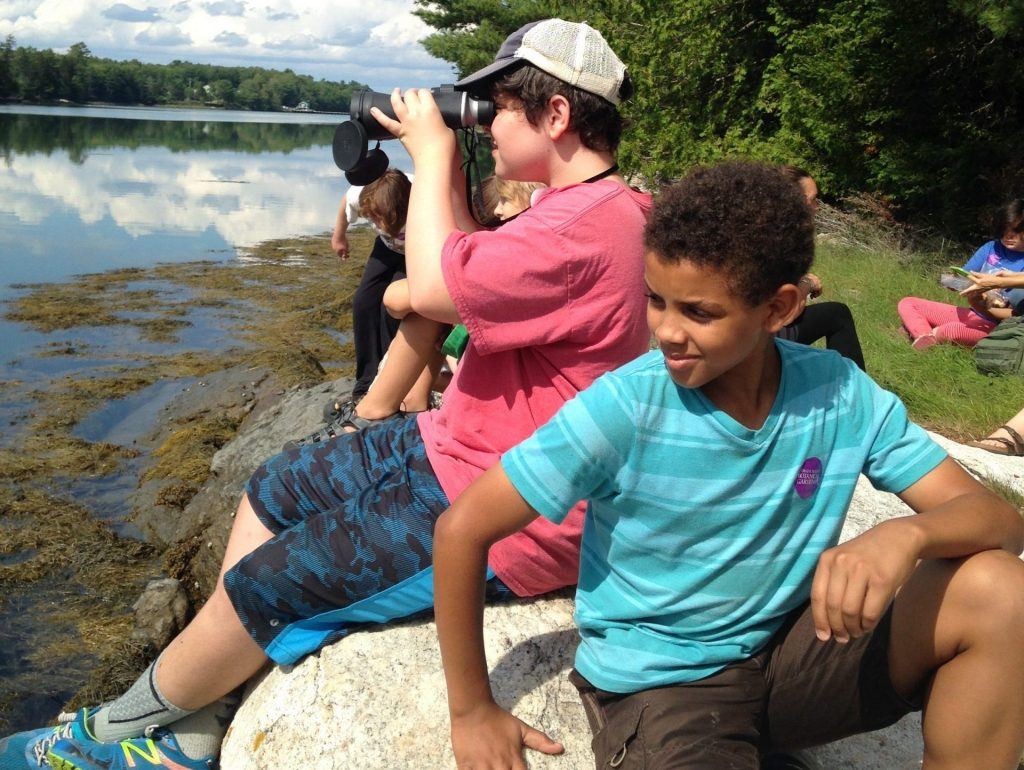 Two students exploring the shore and tidal river, one with binoculars.