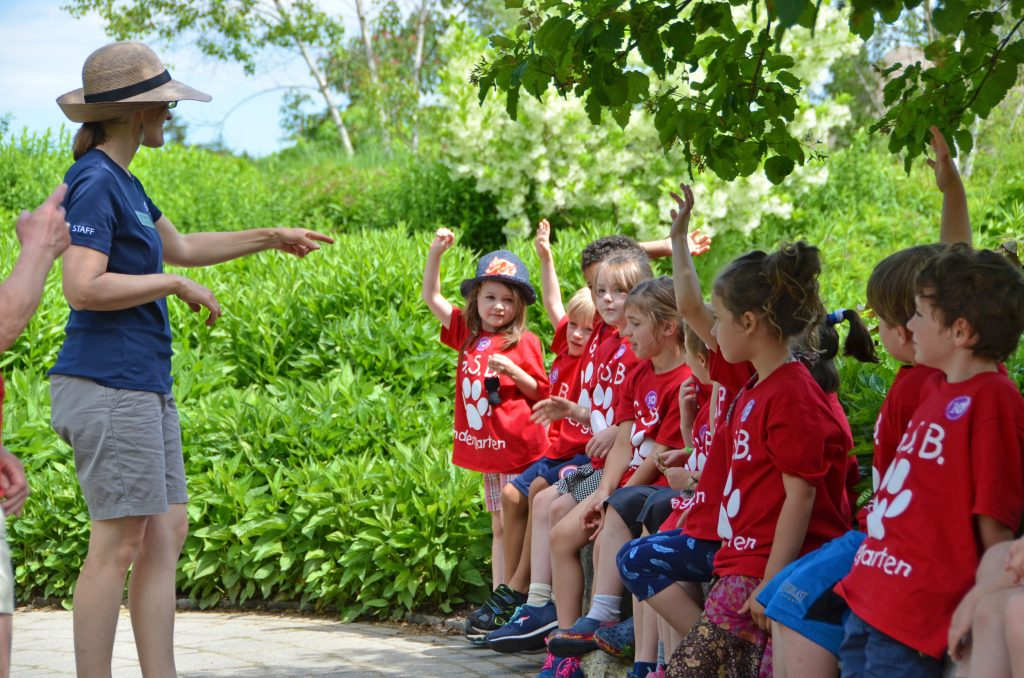 A Gardens staff instructor taking questions from young students sitting along a wall in the Lerner Garden of the Five Senses.