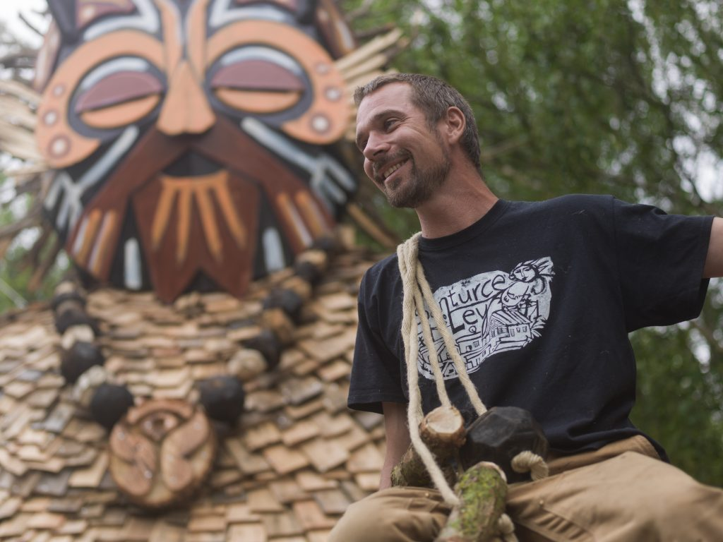 Artist Thomas Dambo smiling while sitting in front of masked giant troll sculpture.